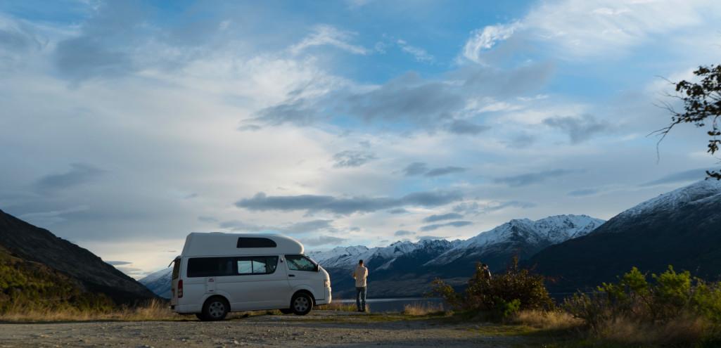 campervan parked beside lake
